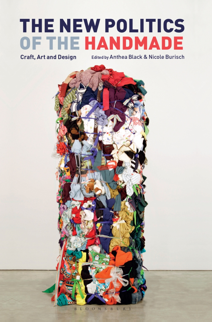 "The book cover for The New Politics of the Handmade: Craft, Art and Design, edited by Anthea Black and Nicole Burisch, with title in navy blue and coral text, featuring an image of the artwork ""Bale Variant no. 0020,"" by Shinique Smith that shows a very tall column of clothes knotted together with fabric strips, installed in a plain gallery space."