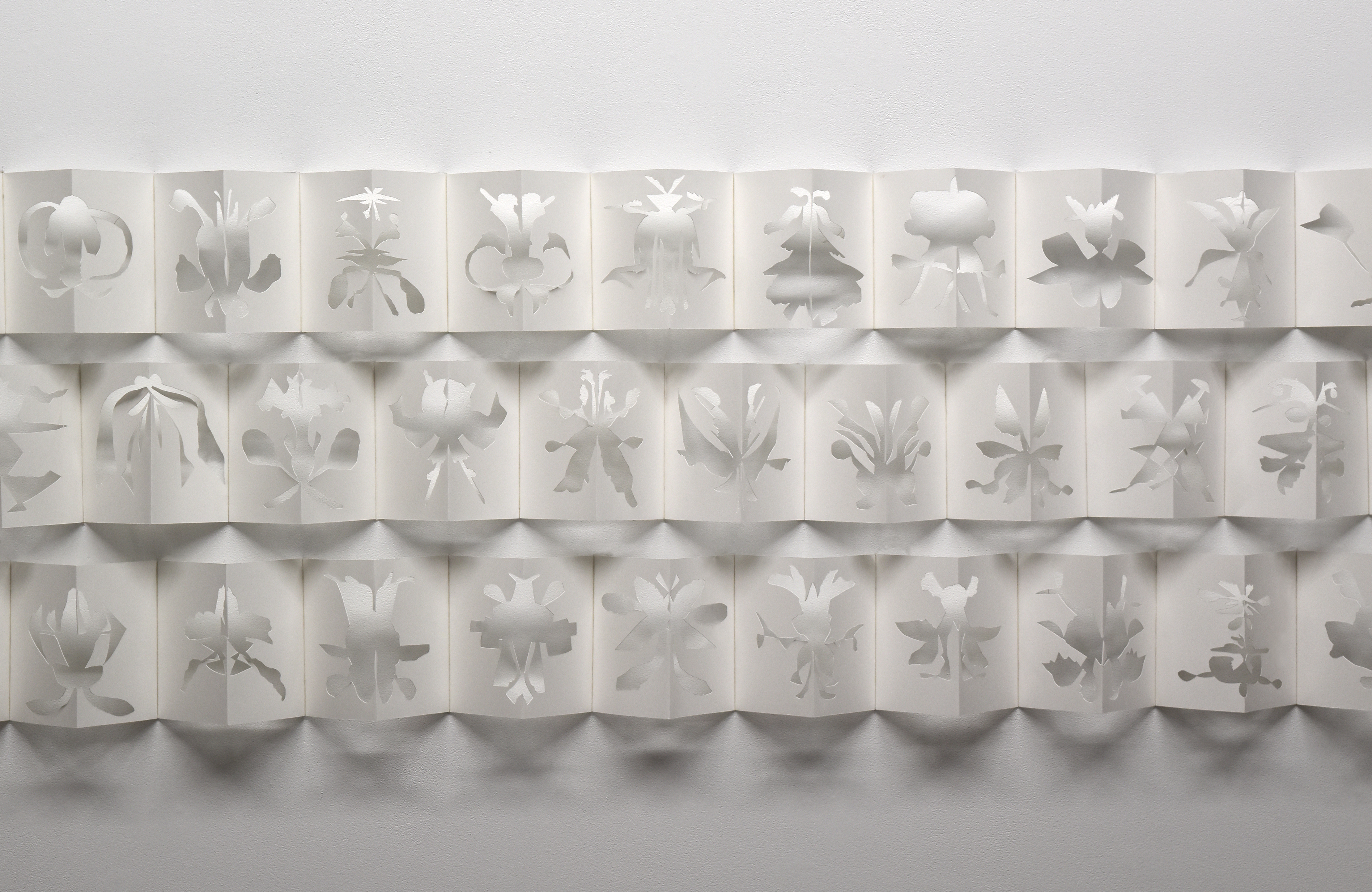 three rows of white, folded accordion-book pages hover on a gallery wall. The pages each have an abstract shape cut out of the centrefold, to create subtle patterns and shadows on the wall.